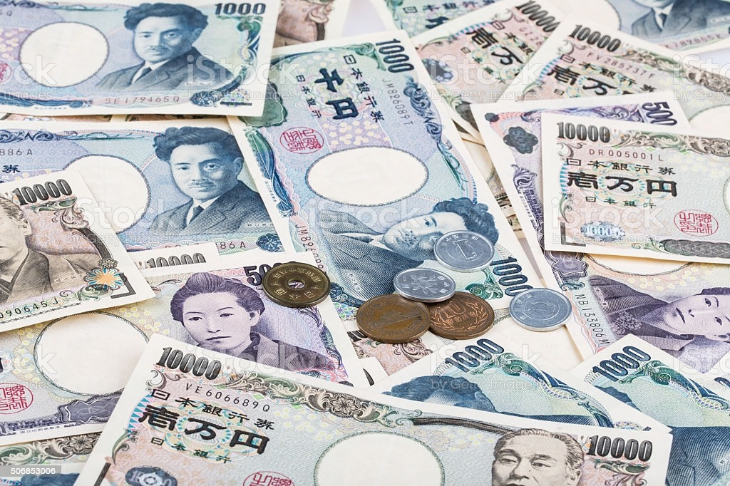 Stack of Japanese currency yen or Japanese banknotes and Japanese yen coins